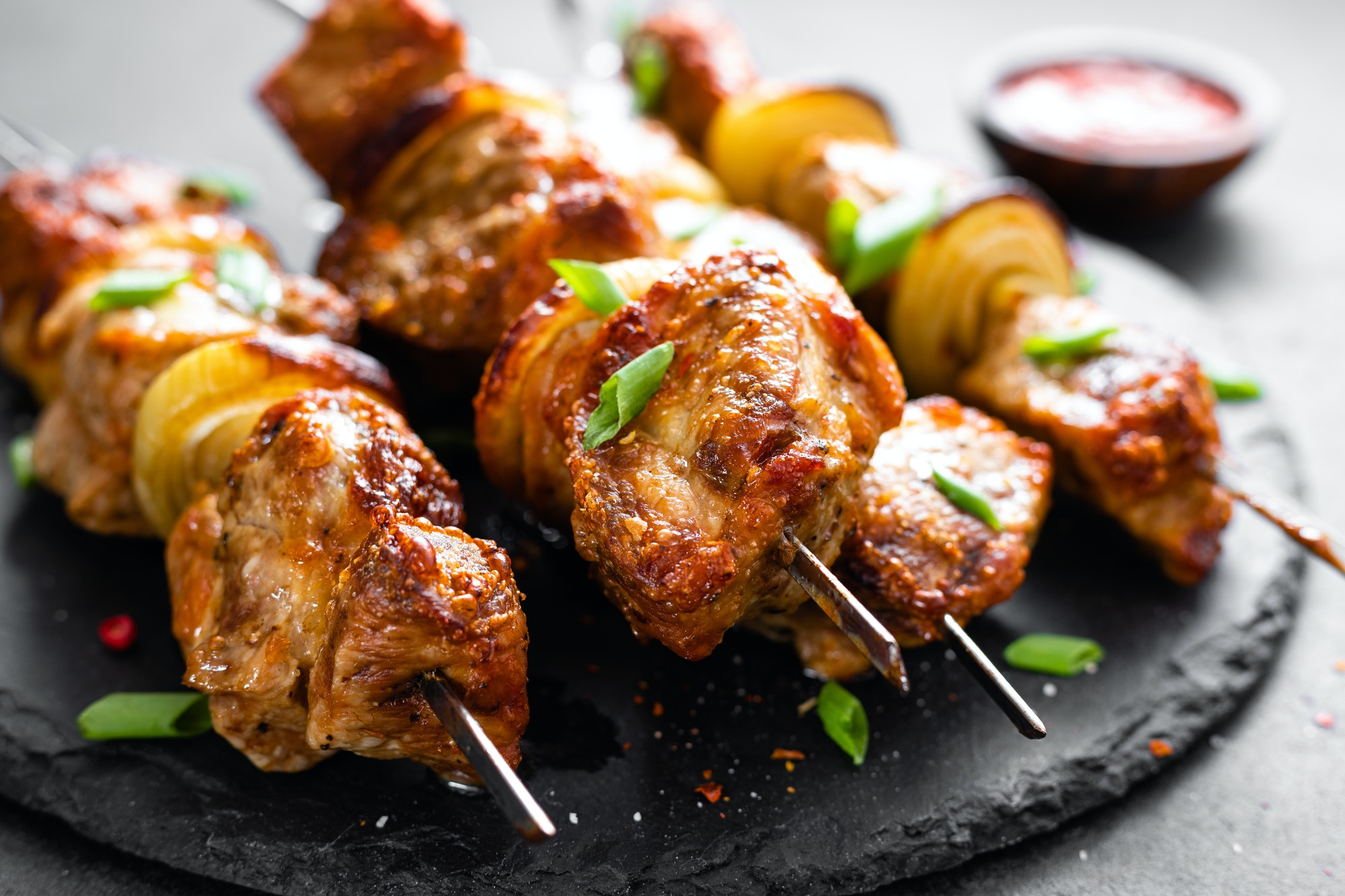 Grilled meat skewers, shish kebab on black background