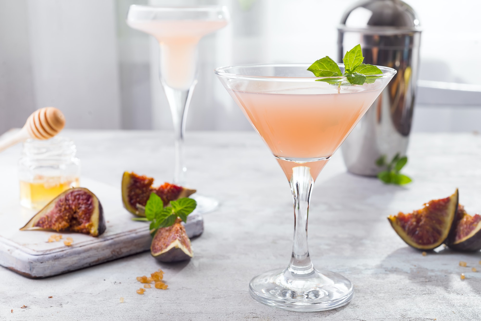 Sparkling pink lemonade martini with figs and honey on light background over windows